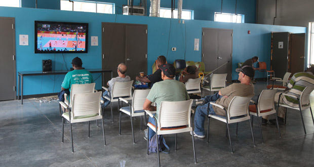 People watch an Olympic Games event on television at the Homeless Alliance day shelter in Oklahoma City.