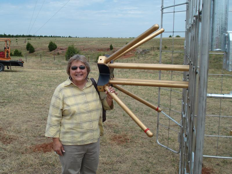 Karen Holp, KGOU General Manager, standing next to a part of the broadcast antenna for KROU was that installed in 2011.