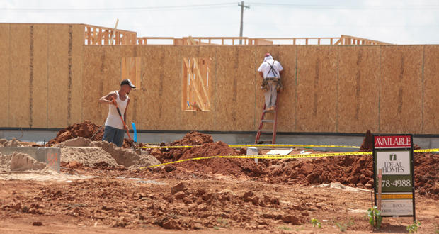 Workers construct new homes at 12th Avenue NW and Tecumseh Road in Norman.