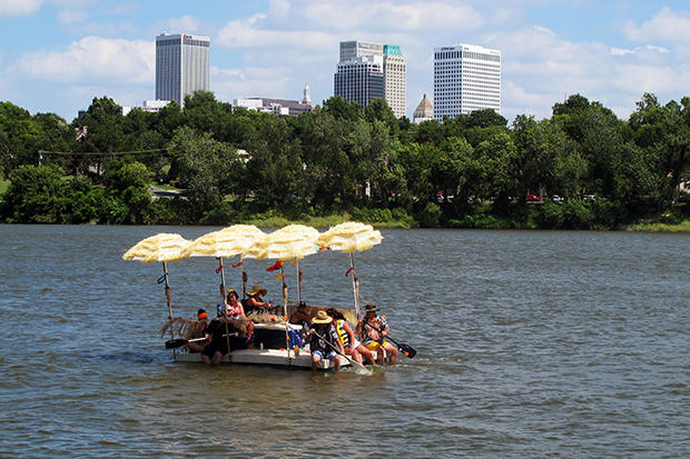 Floaters navigate their homemade raft down the Arkansas River in Tulsa, Okla., during the annual Great Raft Race on Labor Day 2016.