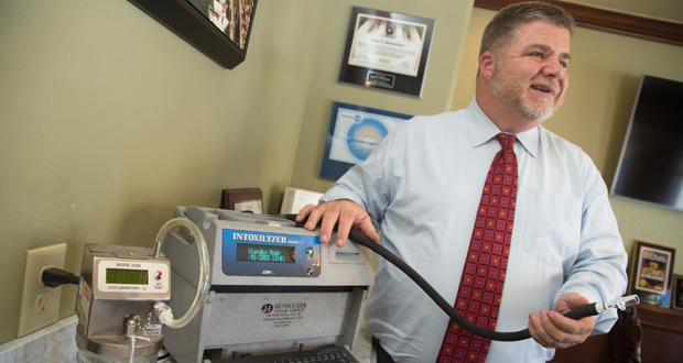 Attorney John Hunsucker stands next to a breath testing machine.
