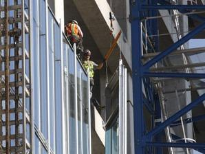 Workers install a glass panel on the new Bank of Oklahoma building in downtown Oklahoma City, August 26, 2016.