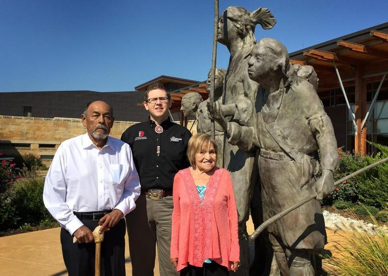 "Chickasaw tribal elders Jerry Imotichey (left) and Hannah Pitmon (right) stand with Joshua Hinson (middle), director of the Department of Chickasaw Language, in front of ""The Arrival"" statue at the Chickasaw Cultural Center in Sulphur, Okla."