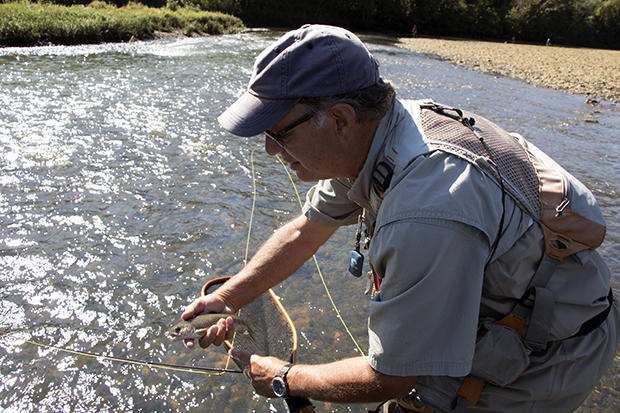 Trout Unlimited's Scott Hood prepares to release this small trout he caught during the group's fishing trip to the Lower Illinois River near the Lake Tenkiller dam in eastern Oklahoma.