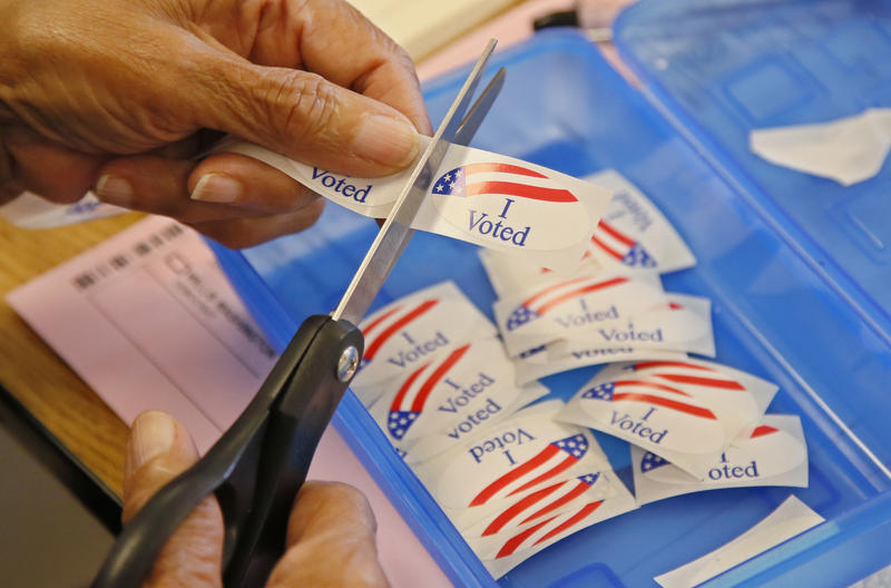 "An elections clerk cuts from a strip of ""I voted"" stickers at a polling place in Oklahoma City, Tuesday, June 28, 2016."