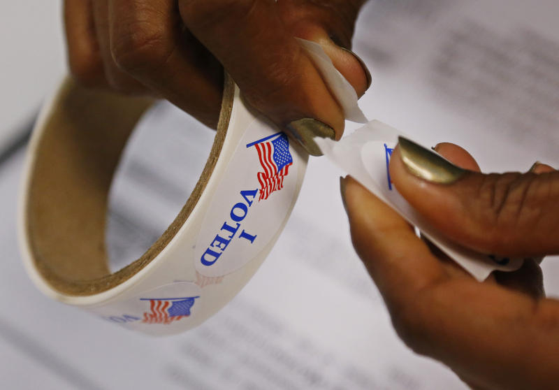 "A poll worker rips ""I Voted"" stickers from a roll at a polling place in Oklahoma City, Tuesday, June 24, 2014."