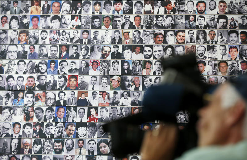 A wall of photographs of journalists killed while reporting the news lines a wall during the rededication of the Journalists Memorial at the Newseum in Washington, Monday, June 9, 2014.