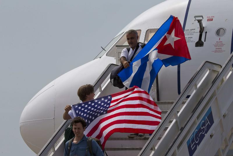 Two passengers deplane from JetBlue flight 387 waving a United States, and Cuban national flag, in Santa Clara, Cuba, Wednesday, Aug. 31, 2016.