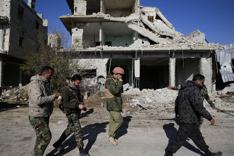 Russian and Syrian army soldiers gather at the last checkpoint before the front line with rebels, in Karam al-Tarab, east of Aleppo, Syria, Sunday, December 4.