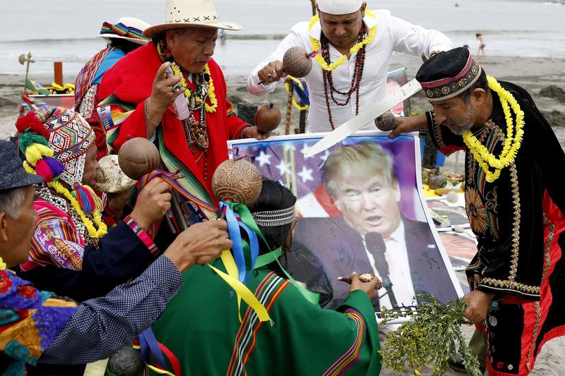 A group of shamans, holding a President-elect Donald Trump poster, perform their annual pre-New Year ceremony, at Agua Dulce beach in Lima, Peru.