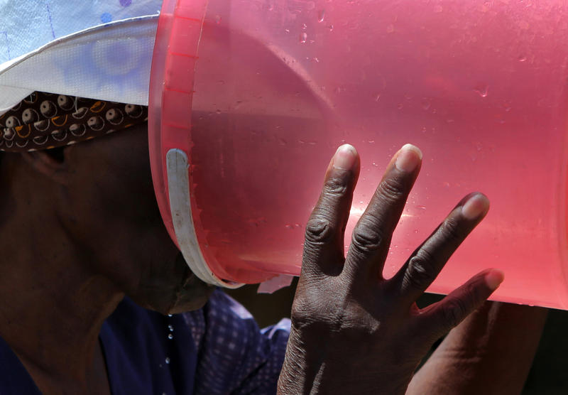 In this Thursday Jan. 7, 2016 photo, an elderly woman drinks water from a bucket after waiting for hours for the municipality to deliver free water, in Senekal, South Africa.