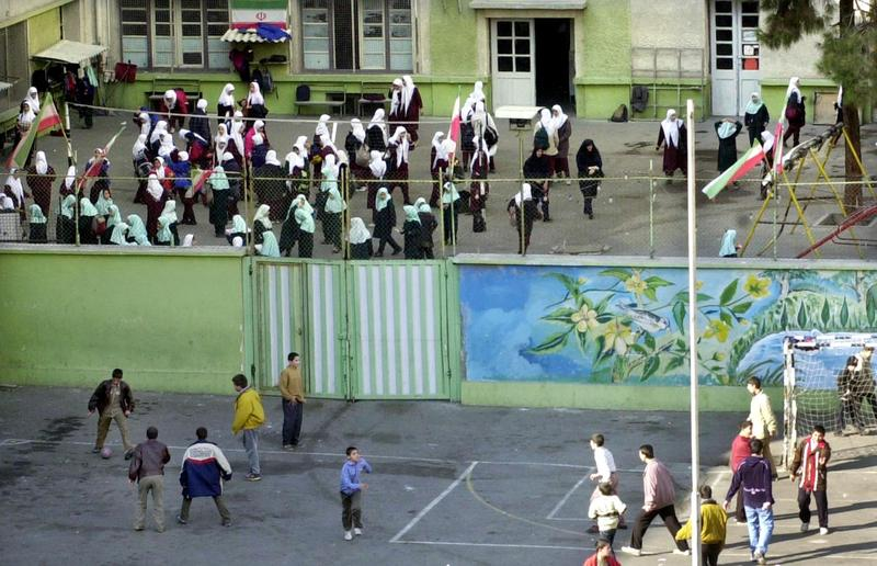 Iranian schoolgirls wearing headscarves, background, gather in a courtyard at a female school as schoolboys play soccer in their school in this photo taken in Feb. 2002 in Tehran.