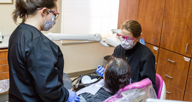 Dental surgeon Jeannie Bath, seated, adjusts the fit on a set of dentures for a patient while volunteer dental assistant Angela Whipple looks on at the Good Shepherd Ministries clinic in Oklahoma City Wednesday.