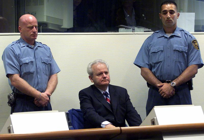 Former Yugoslav President Slobodan Milosevic, center, with court security guards at left and right, appears before the U.N. war crimes tribunal in The Hague, Tuesday July 3, 2001.