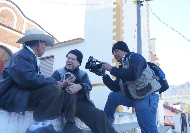 Luis Argueta, center, interviews a man for his film Abrazos.