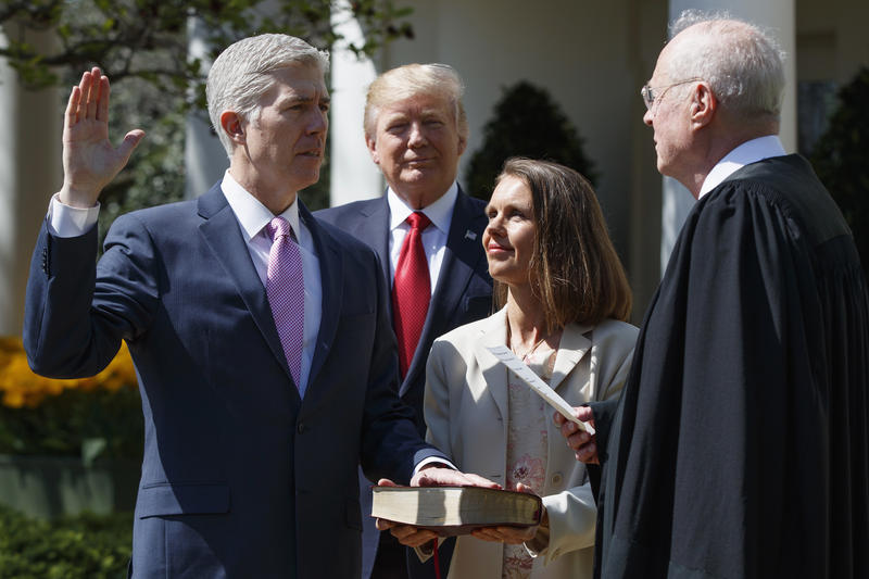 President Donald Trump watches as Supreme Court Justice Anthony Kennedy administers the judicial oath to Justice Neil Gorsuch, accompanied by his wife Marie Louise, during a public swearing-in ceremony in the Rose Garden of the White House in Was