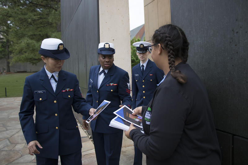 "Kerrian Baker, right, handed programs to ceremony attendees. Baker, 19, works in visitor services at the Oklahoma City National Memorial and Museum, and is too young to remember the bombing. ""I just kind of grew up with it. It was what it was,"" she said."