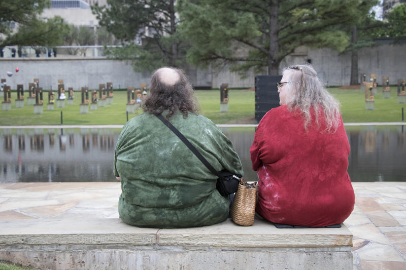 "Dudley Rohde, left, and Eva Bloomer, left, sat on the far edge of the ceremony. For them, the speeches are less important than the public recognition of the victims. ""Someone will say my father's name other than my family,"" said Bloomer. (April 19, 2017)."