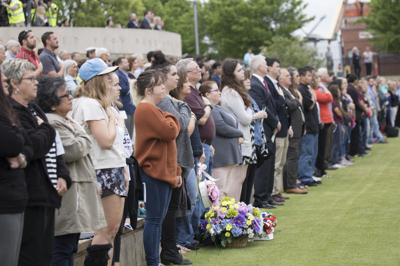 Ceremony attendees, seated along the north side of the reflecting pool, stood for the national anthem, performed by Justin Echols of the Oklahoma City Police Department. (April 19, 2017).