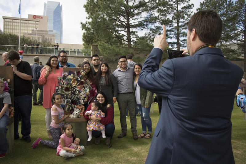 The family of Reverend Gilbert Martinez poses for a photo with the chair bearing his name. Every year, his family, including his five children, grandchildren and others, attends the remembrance ceremony and decorates the chair with family photos, old and