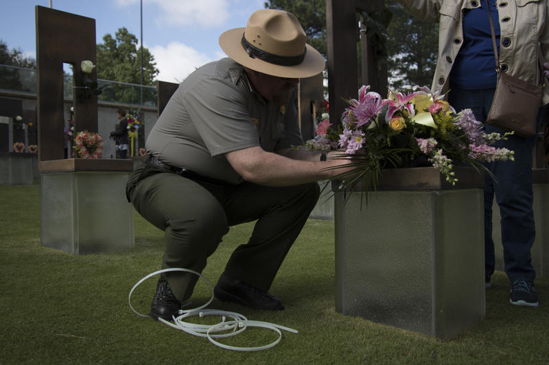 Daniel McKee of the National Park Service helped attach a flower arrangement to a chair bearing Linda Coleen Housely's name. McKee has worked at the memorial for 10 months, but grew up in Oklahoma City and remembers feeling the shockwave of the explosion
