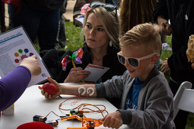 Shannon Williams watches her son as a neuroscientist shows him how to control a grabber-arm by squeezing his hand.
