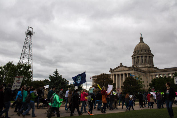 Marchers fly and earth flag between an oil well and the Oklahoma capitol building on the last leg of the March for Science.