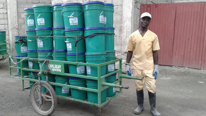 A worker with a SOIL collection cart in Haiti.
