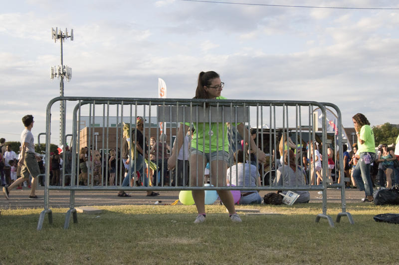 A Pride volunteer picks up barriers after the parade.