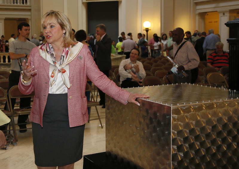 Oklahoma Gov. Mary Fallin talks with the media as she leans on a stainless steel time capsule to be opened in 100 years, following a ceremony at the state Capitol in Oklahoma City, Monday, June 26, 2017. The box will be filled with artifacts, sealed and p