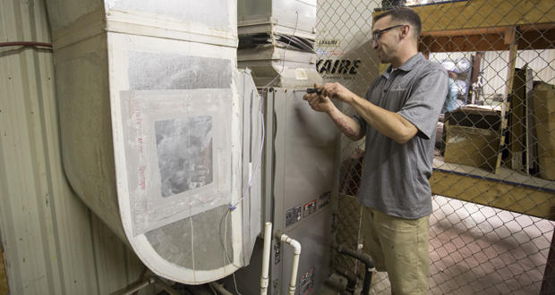 Service technician Tyler Pabst demonstrates the servicing of a geothermal unit in Norman Wednesday.