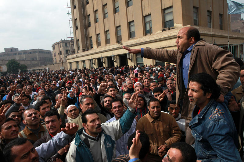 In this photo taken Saturday, Feb. 15, 2014, textile workers strike to demand a minimum wage, the removal of their company's head and the head of the firm's holding company, and back pay of yearly bonuses in Mahalla al-Kobra, Egypt.