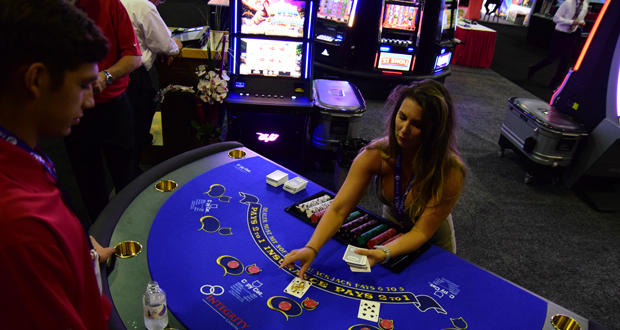 Katelyn Holbrook, with Integrity Gaming, practices dealing cards to Rustin Martin, also with Integrity, at the Oklahoma Indian Gaming Association's annual conference in Oklahoma City.