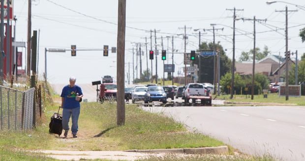 A woman pulls a suitcase along NE 23rd Street near N. Spencer Road in Oklahoma City.