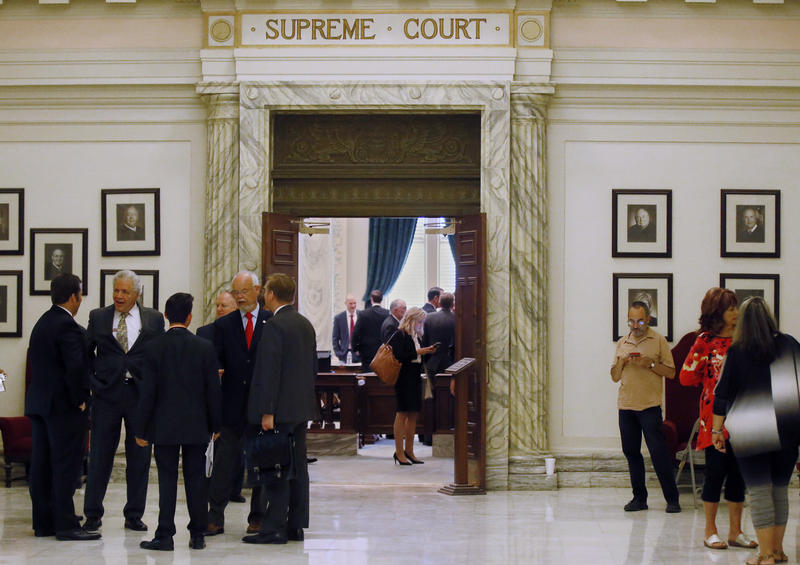 People wait outside the Oklahoma Supreme Court during a break in oral arguments in connection with three lawsuits that challenge revenue-raising measures adopted by lawmakers, in Oklahoma City, Tuesday, Aug. 8, 2017.