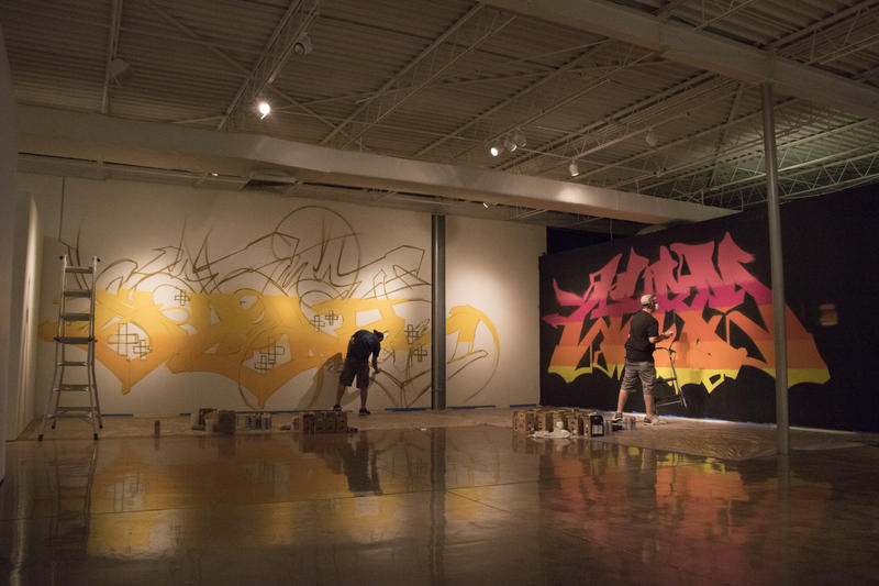 Artists paint on the walls of the Oklahoma Contemporary during the installation of Not for Sale.
