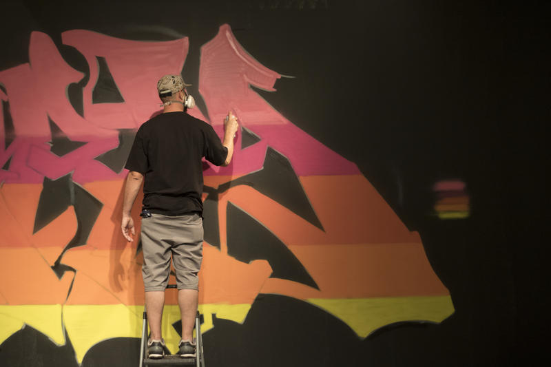 Artist GERM spray paints a wall at the Oklahoma Contemporary.