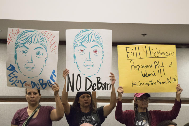 Activists hold signs supporting the renaming of DeBarr Avenue at a Norman City Council meeting on Tuesday night.