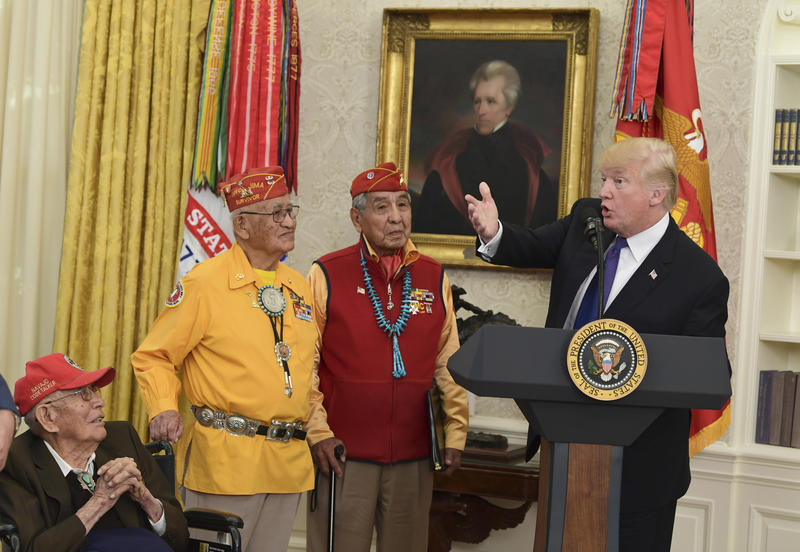 President Donald Trump, right, speaks during a meeting with Navajo Code Talkers including Fleming Begaye Sr., seated left, Thomas Begay, second from left, and Peter MacDonald, second from right, in the Oval Office of the White House in Washington, Monday,