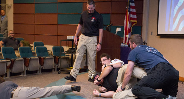 Capt. Tony Riddles of the Norman Police Department, standing, watches as three volunteers from the audience tackle Sgt. Tim Smith, who acted as an armed gunman for an active shooter training workshop at Norman Regional Hospital on November 17, 2017.