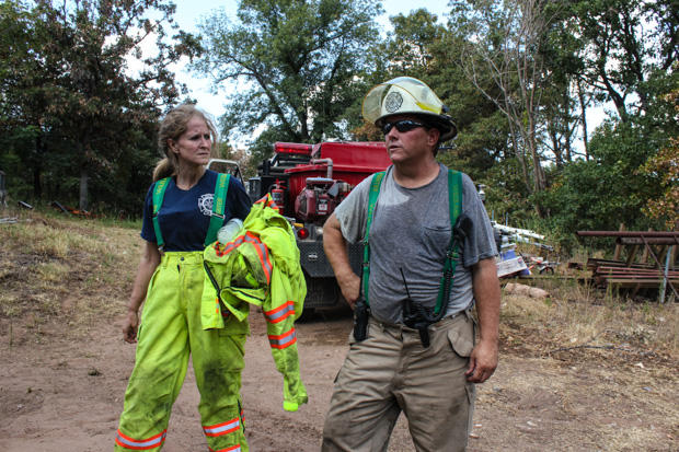 Volunteer firefighters Christie Smith and David Thompson cool down after extinguishing a hotspot that flared east of Noble, Okla., in 2012. Scientists expect the risk of wildfire to increase as climate change-fueled droughts occur more frequently.