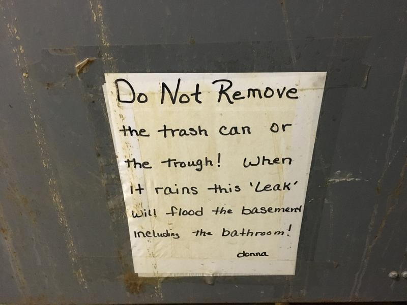 A handwritten sign at the state penitentiary reminds staff not to remove the trash can that catches water from leaks.