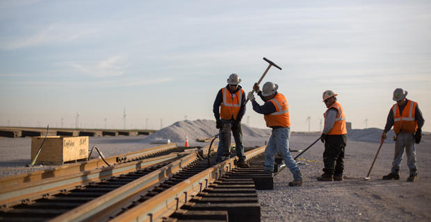 Workers hammer spikes into place on a new rail spur south of Kingfisher.