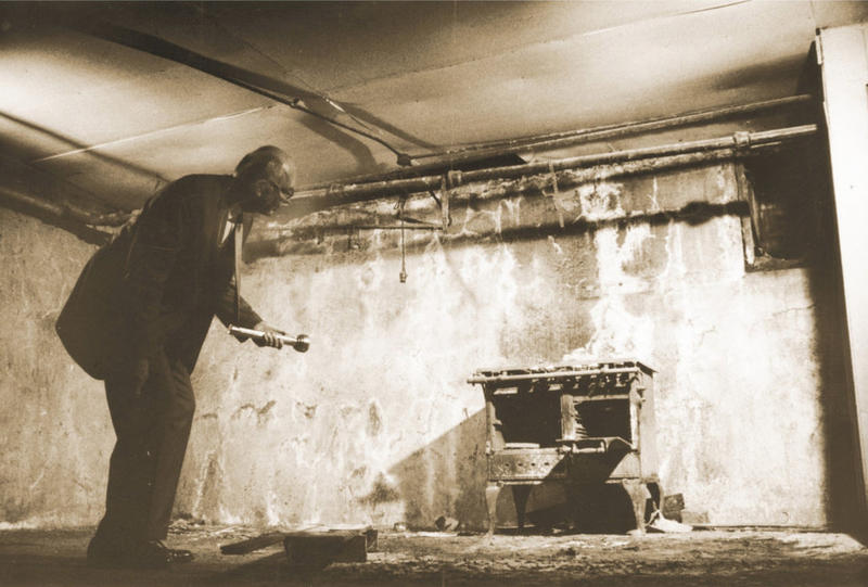 "Former Oklahoma City mayor George Shirk examines an old stove in the Chinese ""city"" under Oklahoma City, 1969."