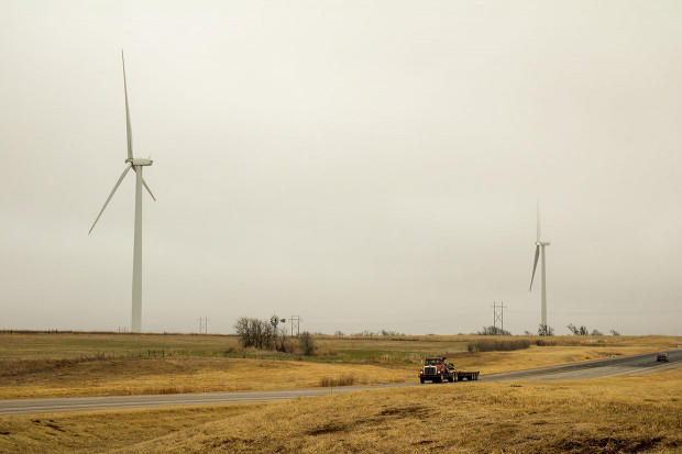 A line of wind turbines spin near Seiling, Okla.