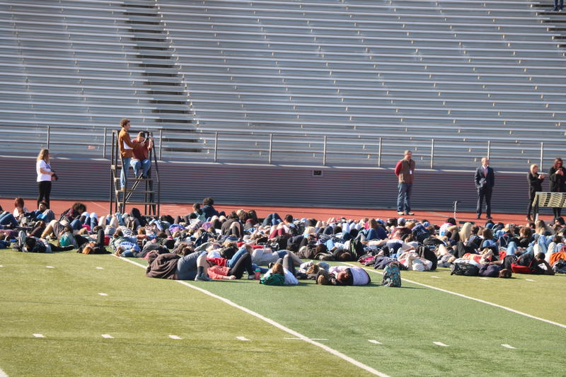 Students at Norman High School lie down to represent the victims of mass shootings at schools.