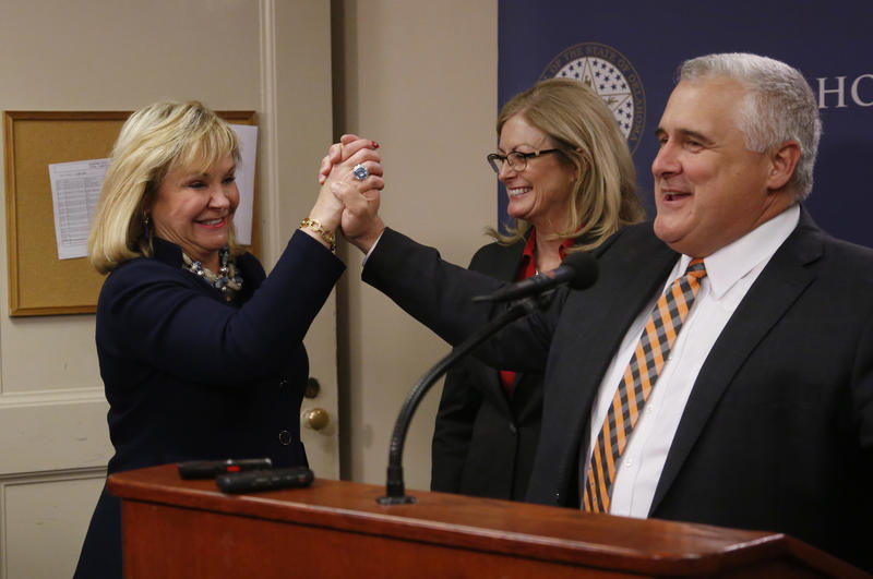 Oklahoma Gov. Mary Fallin, left, high-fives Sen. Mike Schulz, right, R-Altus, during a news conference following a vote on a package of tax hikes to fund teacher pay raises in Oklahoma City, Wednesday, March 28, 2018. Sen. Kim David, R-Porter.