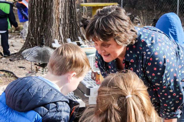 Preschool teacher Basset speaks with a student in an outdoor area at St. Charles Borromeo Catholic School in Oklahoma City.