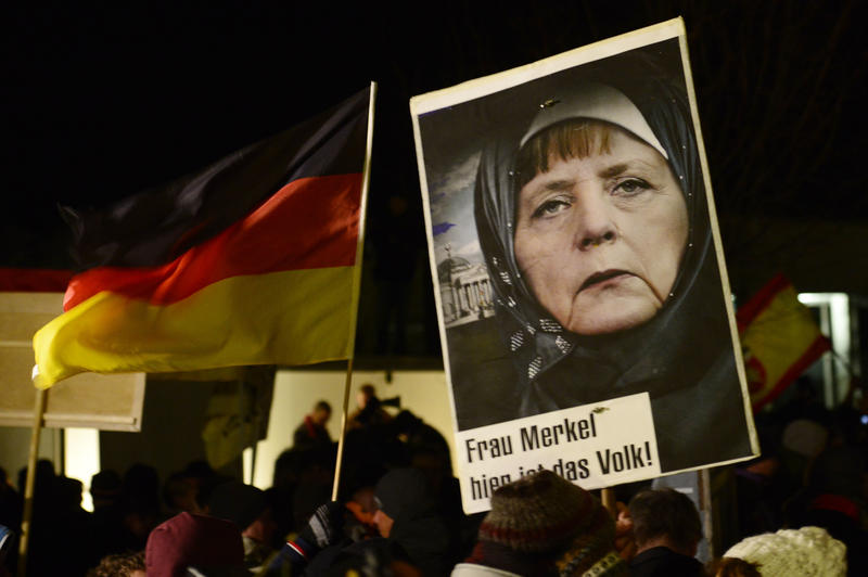 On Jan. 12, 2015 a protestor holds a poster with an image of German Chancellor Angela Merkel wearing a headscarf in front of the Reichstag building with a crescent on top during a rally.