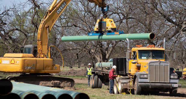 Workers at a site of a pipeline under construction along state Highway 75 north of Horntown.